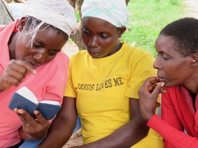 three women reading a Bible together
