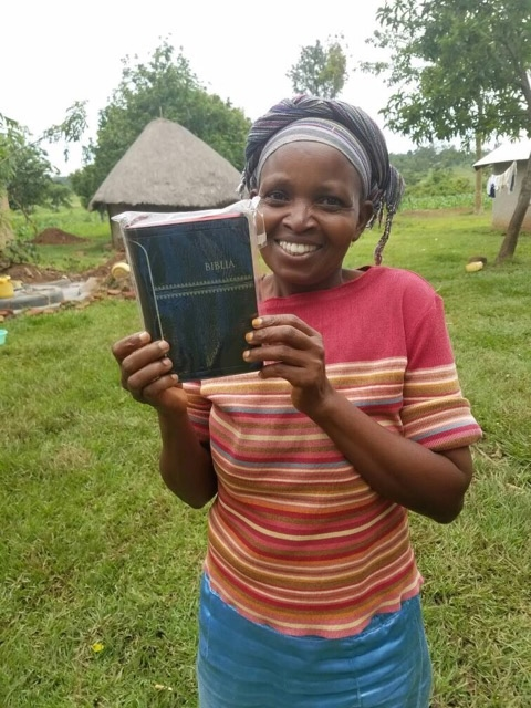 a smiling woman holding a new Bible